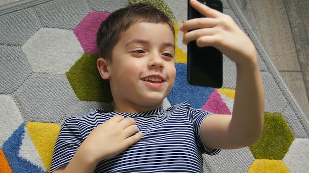 Niño sonriente mano sosteniendo teléfono móvil o teléfono inteligente haciendo selfie retrato foto o video llamada conferencia