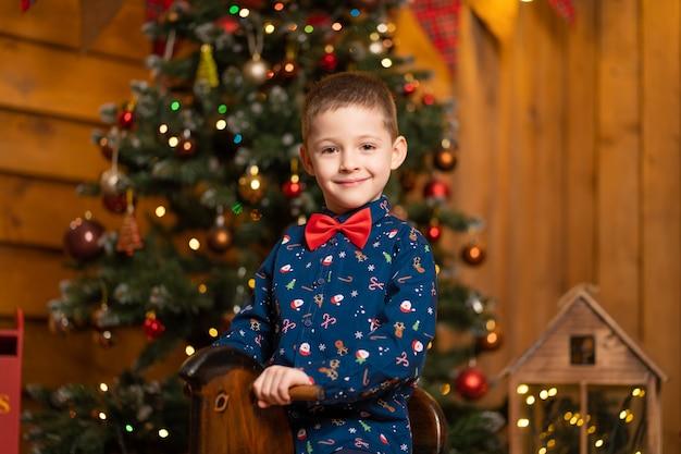 Niño sonriente en una mecedora para navidad