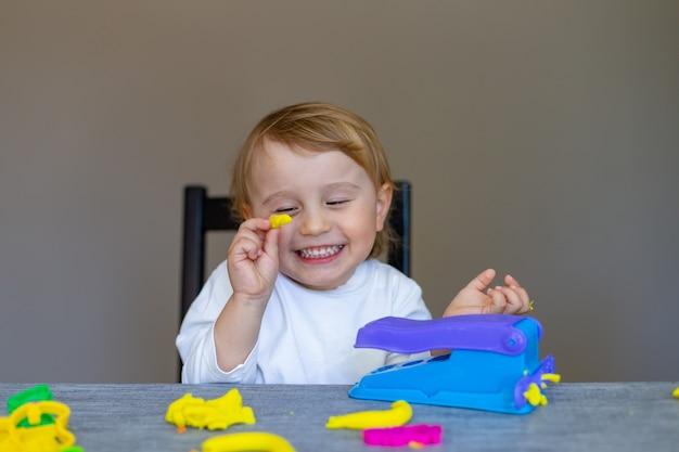 Niño sonriente moldes de plastilina de colores en la mesa