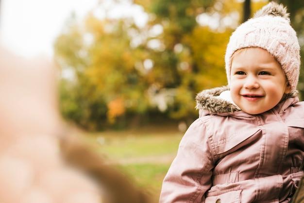 Niño sonriente en el parque de otoño