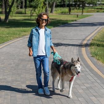 Niño sonriente en el parque paseando al perro