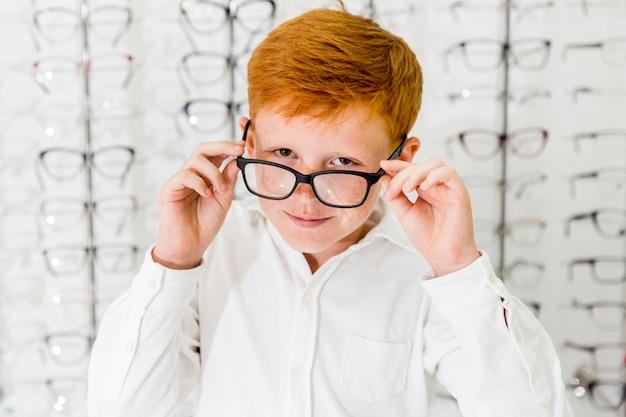Niño sonriente con pecas en su rostro con gafas y mirando a cámara