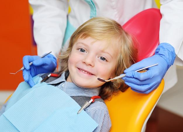 Niño sonriente con el pelo rizado claro en el examen en la silla dental