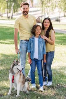 Niño sonriente con perro posando con sus padres en el parque