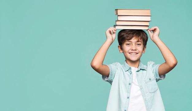 Niño sonriente con pila de libros en la cabeza.