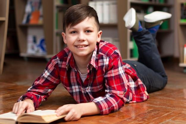 Niño sonriente en el piso leyendo
