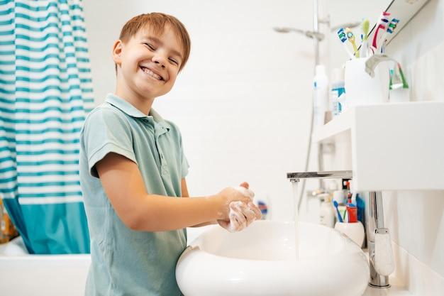Niño sonriente preescolar lavarse las manos con jabón debajo del grifo con agua.