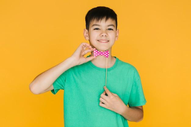 Niño sonriente probándose una pajarita falsa