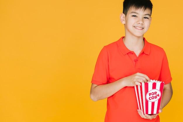 Niño sonriente que tiene palomitas de maíz con espacio de copia