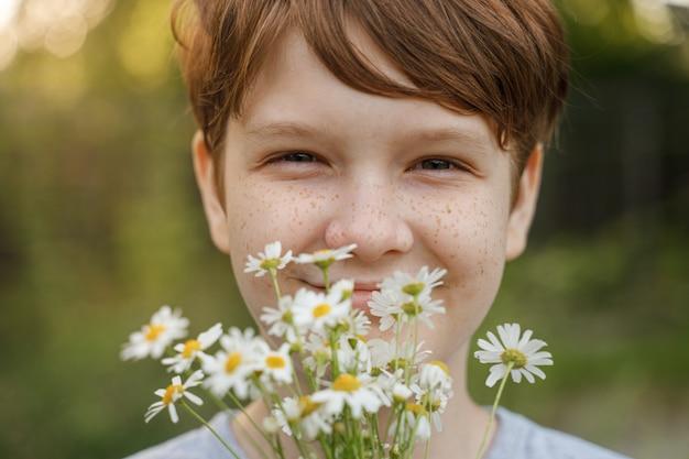 Niño sonriente con un ramo de margaritas blancas.