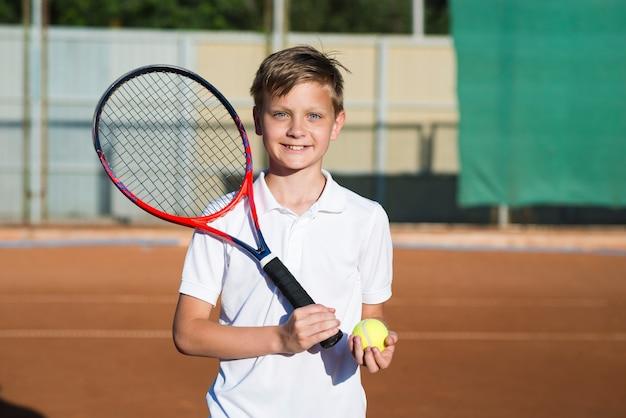 Niño sonriente con raqueta de tenis