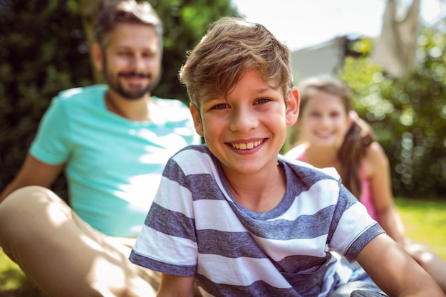 Niño sonriente, sentado en el jardín con padre y hermana