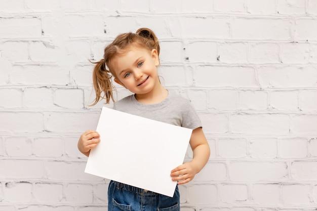 Niño sonriente sobre pared de ladrillo blanco sosteniendo la hoja de papel vacía blanca
