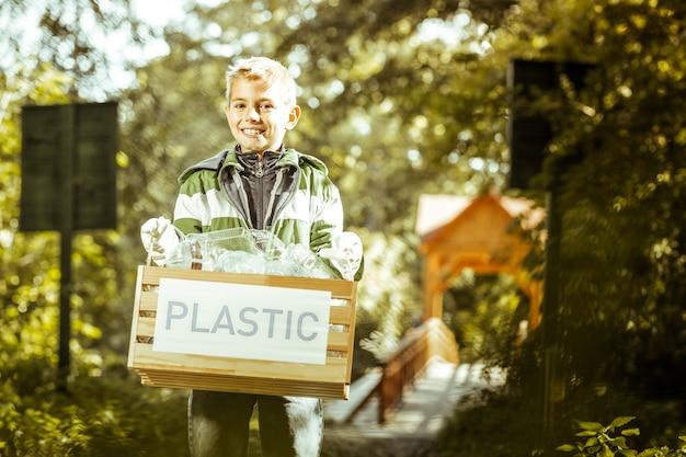 Un niño sonriente sosteniendo una caja de basura plástica en el bosque en un buen día