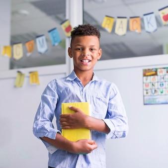 Niño sonriente sosteniendo un libro en clase