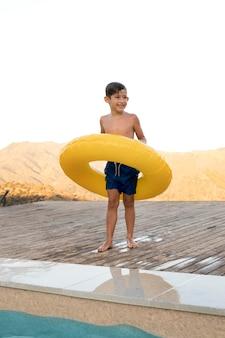 Niño sonriente de tiro completo con aro salvavidas