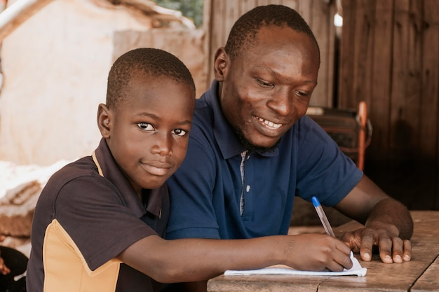 Niño sonriente de tiro medio escribiendo