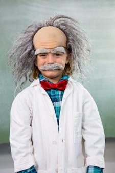 Niño sonriente vestido como científico de pie contra el tablero