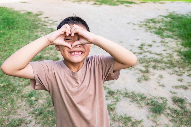 El niño sonrió felizmente feliz, en forma de corazón con las manos.