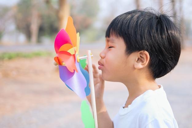 Niño soplando un molino de viento de juguete por la mañana en el parque