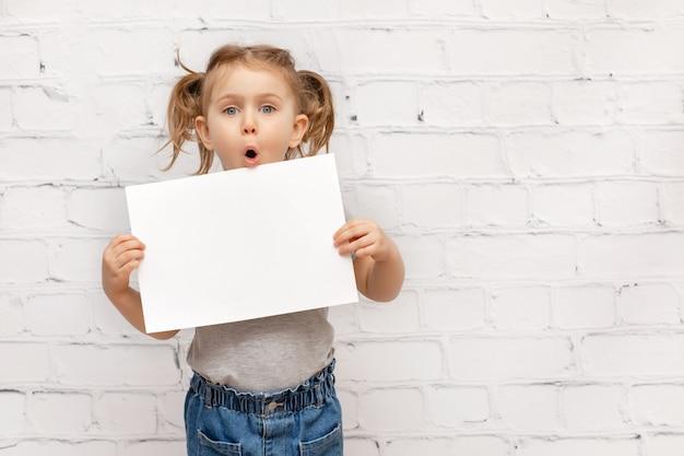 Niño sorprendido sobre pared de ladrillo blanco con hoja de papel blanco