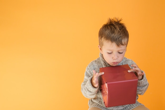 Niño sorprendido en suéter mirando el regalo sobre fondo naranja.