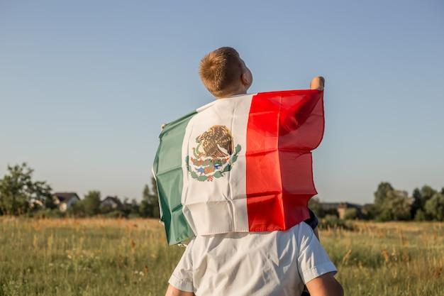 Niño sosteniendo la bandera de méxico.