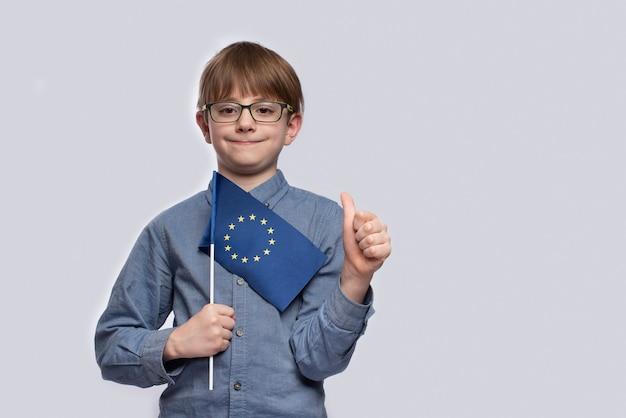 Niño sosteniendo una bandera de la ue y muestra un gesto bien hecho