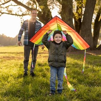 Niño sosteniendo una cometa sobre su cabeza.