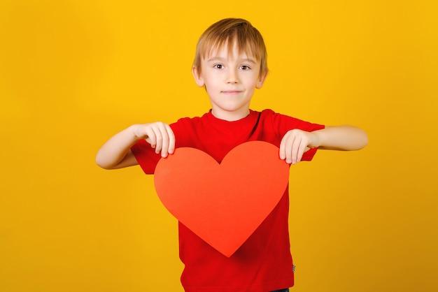 Niño sosteniendo corazón rojo