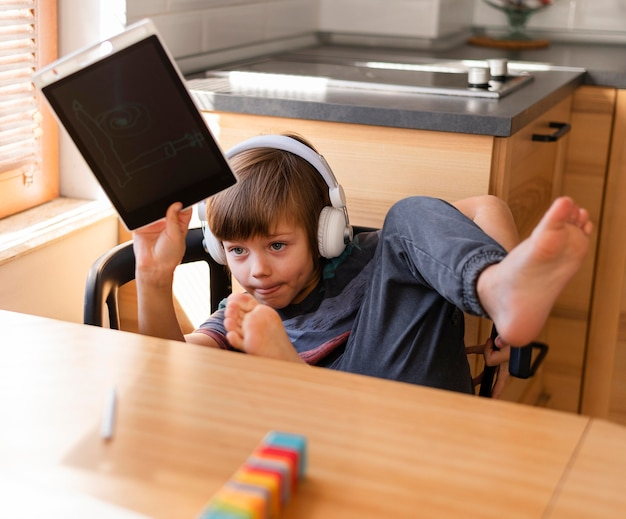 Niño sosteniendo un dibujo interacciones escolares en línea