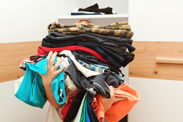 Niño sosteniendo una enorme pila de ropa. kid hace orden en el armario. organización de almacenamiento. ropa infantil de segunda mano para reutilización, reventa, reciclaje y donación.