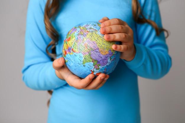Niño sosteniendo un globo terráqueo