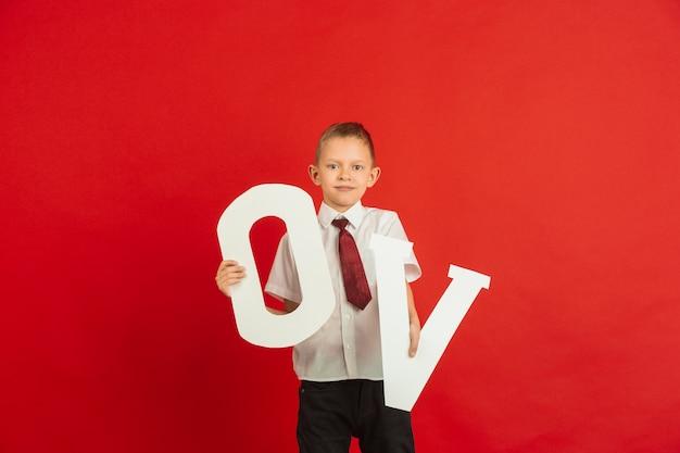 Niño sosteniendo las letras o y v