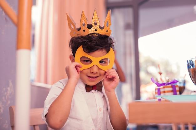 Niño sosteniendo linda máscara mientras está en la fiesta de cumpleaños