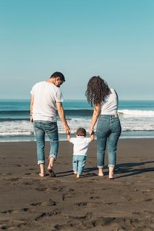 Niño sosteniendo las manos de los padres y caminando en la playa