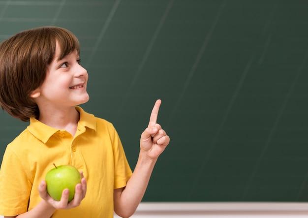 Niño sosteniendo una manzana mientras apunta hacia arriba