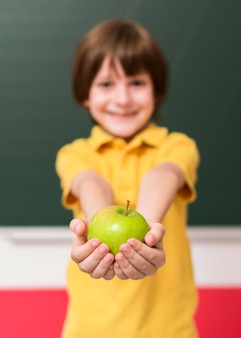 Niño sosteniendo una manzana verde