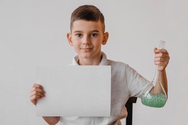 Niño sosteniendo un papel en blanco y un recipiente de química