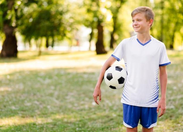 Niño sosteniendo una pelota de fútbol al aire libre con espacio de copia