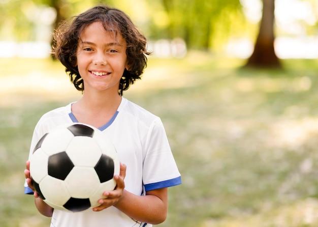 Niño sosteniendo una pelota de fútbol con espacio de copia