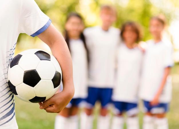 Niño sosteniendo una pelota de fútbol junto a sus compañeros de equipo desenfocado