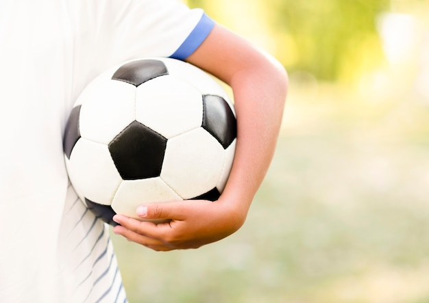 Niño sosteniendo una pelota de fútbol con primer plano de espacio de copia