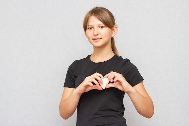 Niño sosteniendo un pequeño corazón rosa. símbolo de amor.