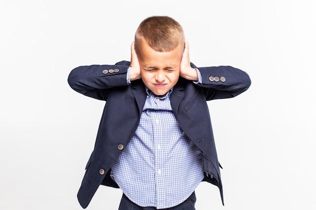 Niño sosteniendo sus manos contra sus orejas una pared blanca