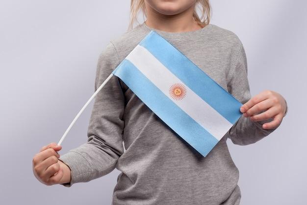 Niño sostiene la bandera de argentina en sus manos. de cerca