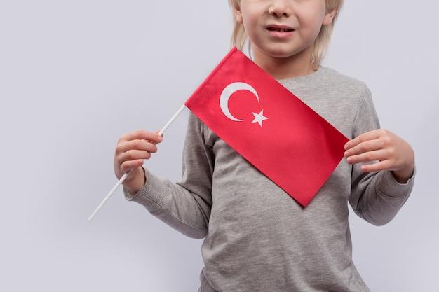 El niño sostiene la bandera de turquía. de cerca. aprender turco para niños. inmigración a turquía