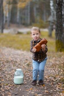 El niño sostiene una barra de pan con leche cerca.
