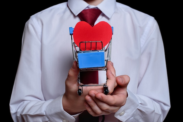 Niño sostiene un carrito de compras de metal con una postal en forma de corazón dentro