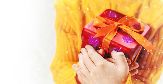 El niño sostiene una decoración y regalos de la navidad en un fondo blanco. enfoque selectivo